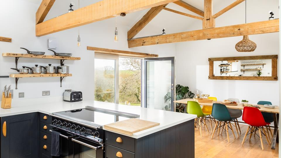 The kitchen and dining area has the perfect space for entertaining, the bespoke dining table has urban metal standing with the reclaimed wood surface with retro colour pop chairs.