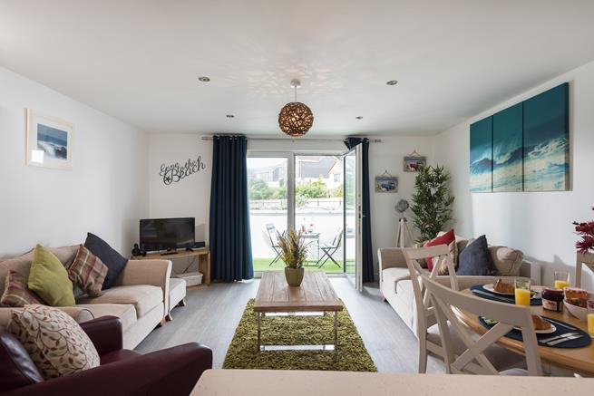 Open plan living space with dining area and patio doors leading to private balcony