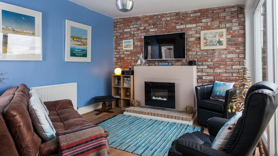 The sitting room has a great retro style, with a trendy sofa and two chairs, there are patio doors leading out into the courtyard.