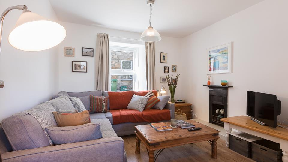 The sitting area has been tastefully decorated to have a contemporary theme but keeping the character of the cottage with its original fireplace maintained.