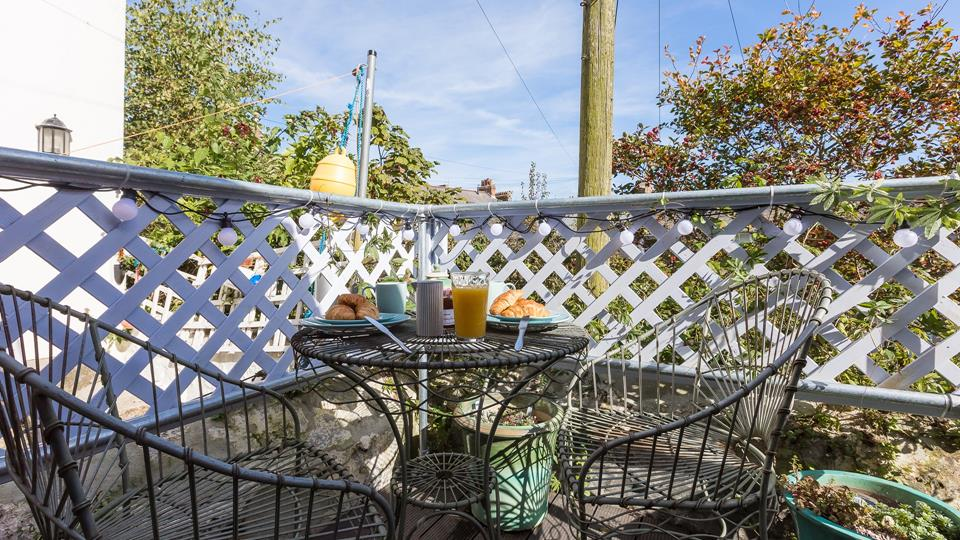 The decking area has a lattice fence for seclusion and privacy with a metal bistro table and chairs.