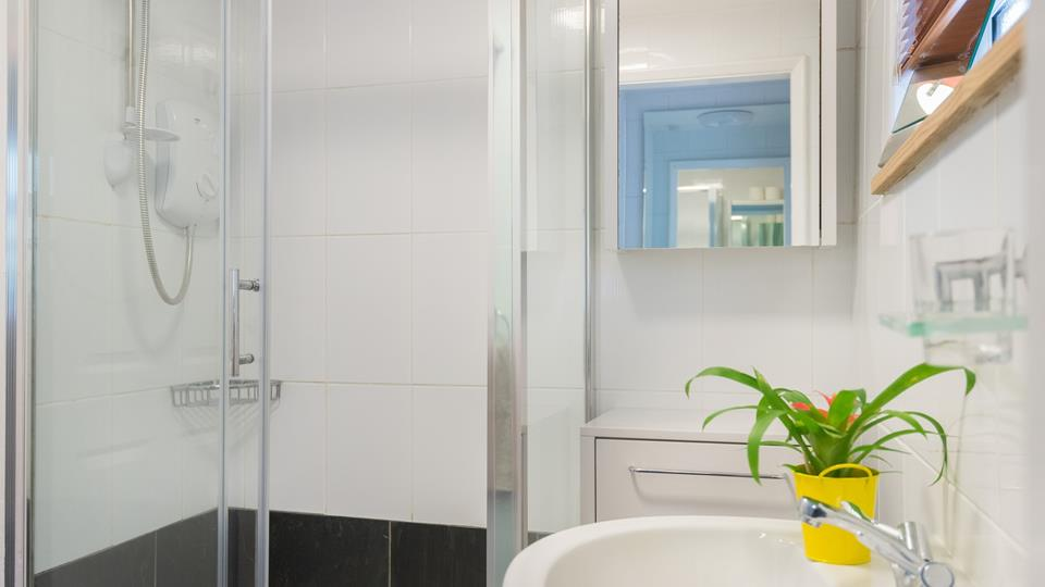 Bright and fresh, the ensuite with shower is comfortably sized for two.