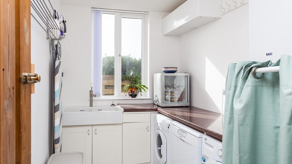 A downstairs utility room offers a convenient space to pop clothes in the wash after a day out.