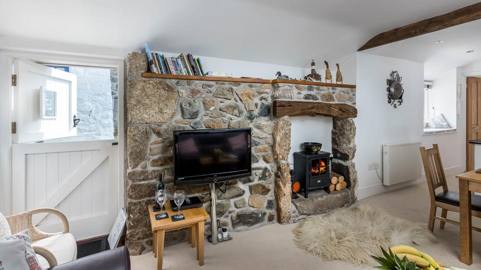 The sitting area faces a cosy log burner, set in a traditional exposed granite wall.