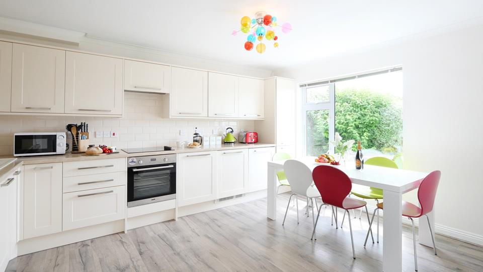 The well-proportioned kitchen/dining room is ideal for family meals together. Colour pop accent chairs and lighting achieve a contemporary vibe.