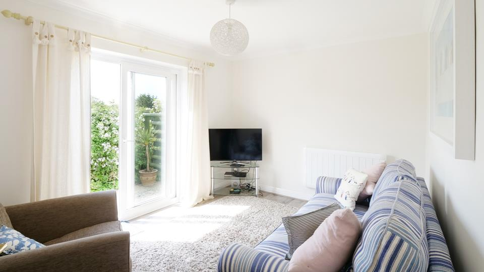 Light and airy, the comfortable sitting room has patio doors leading to the private garden area.