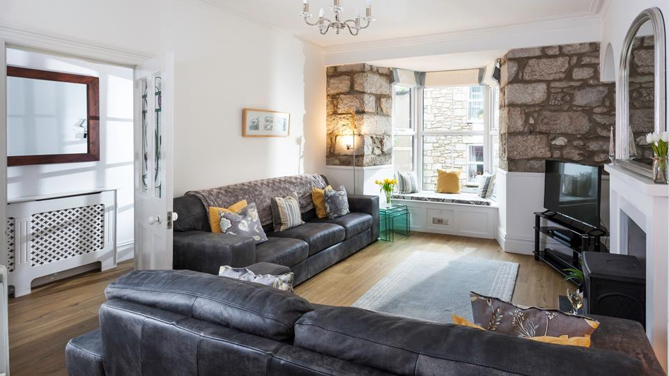 The living space has two leather sofas a large bay window with a padded seat and exposed granite stone-faced accent wall.