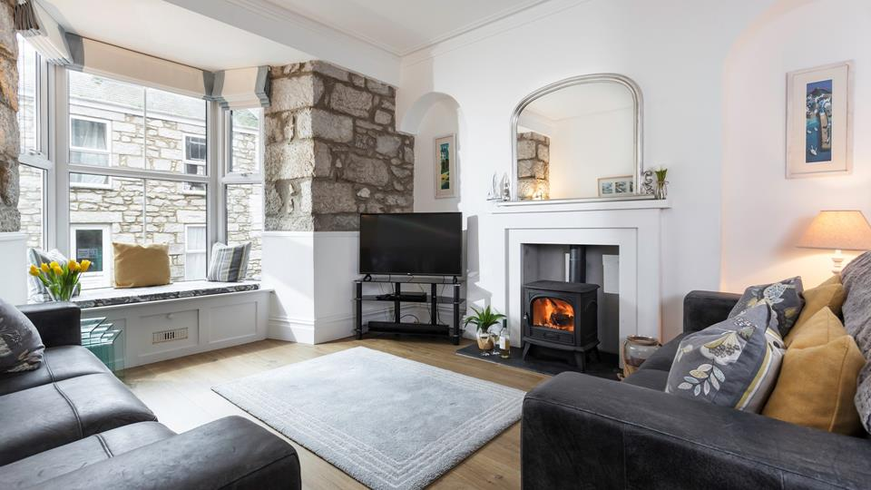 The living space has a wood burner in the fireplace with an arched mantle mirror above and slate hearth.