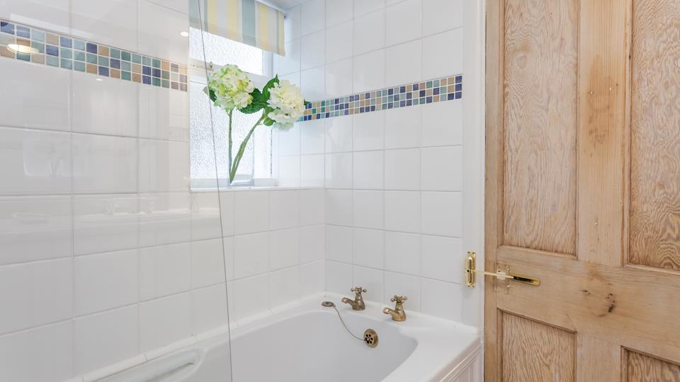 Enjoy a relaxing bubble bath at the end of the day, or have a refreshing shower using the shower over in this comfortable bathroom.