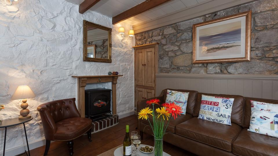 The traditional sitting room has so much character with exposed beams, original fireplace and stone wall with a semi wood-clad finish.