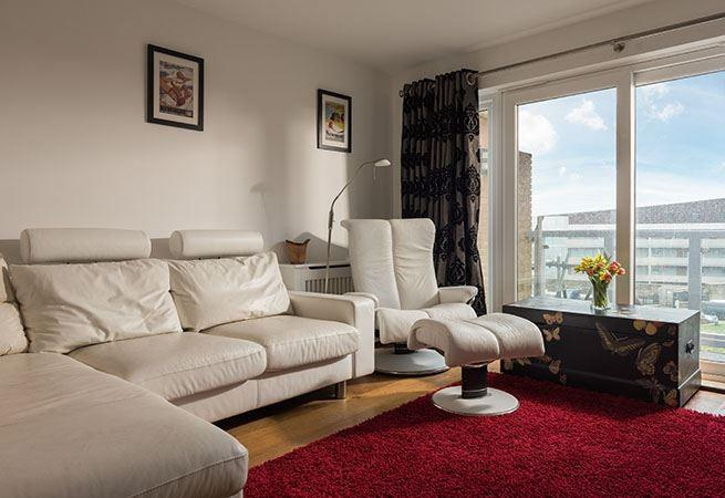 Sitting area with doors to balcony and sea views.
