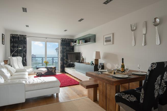 The sociable open plan living area, enjoys comfortable furnishings and doors out onto the balcony.
