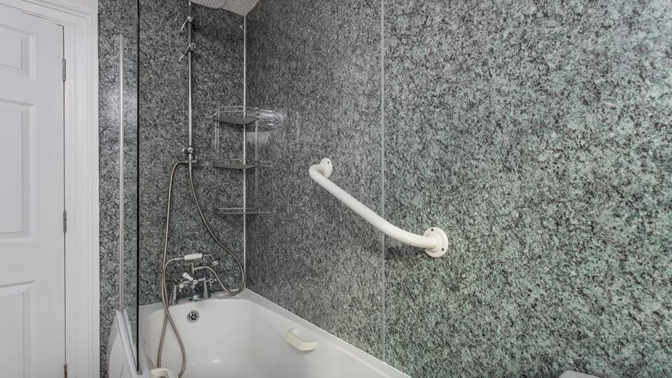 The family bathroom has a good-sized bath with a fixed rainfall showerhead and additional handheld shower attachment, there is also a grab rail to assist with bathing.