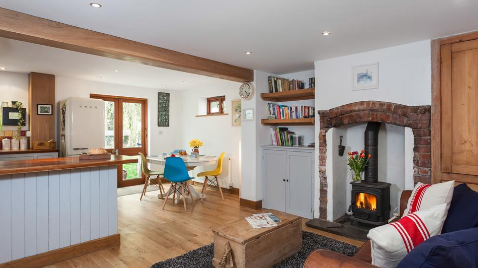 The open plan kitchen, dining and sitting room space has a lovely laid back feel, relax by the wood burner and cosy up on the comfy leather sofa.