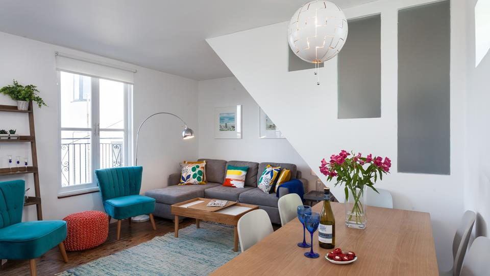 The living space has a grey textile corner sofa with two teal velvet accent chairs and an orange marl knitted footstool.