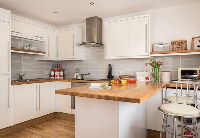 The well equipped kitchen with breakfast bar is the perfect place for reading a paper in the morning.