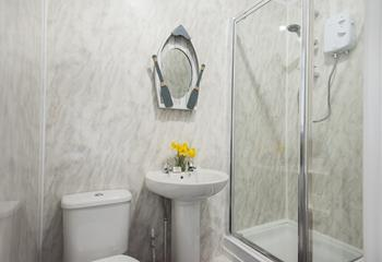 The seaside themed decor continues into the bathroom which has a shower, WC and basin.