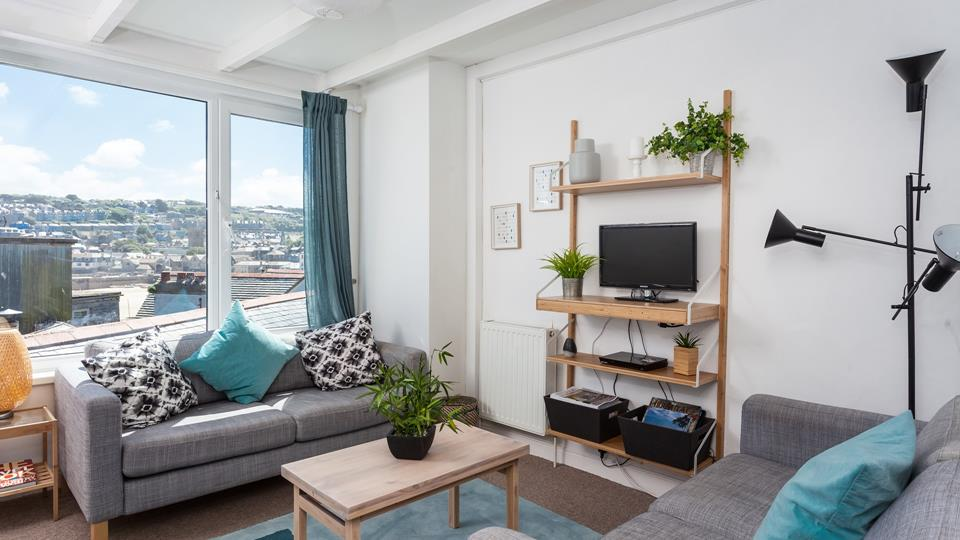The living room has a contemporary style with two grey sofas and a view across St Ives Harbour and town.