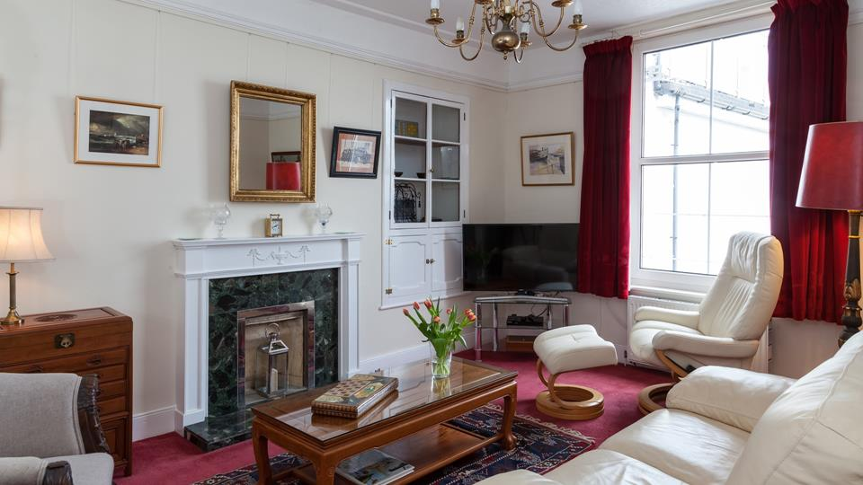 The sitting room has quirky decor, a granite feature fireplace and vintage dark wood dresser provide plenty of character.
