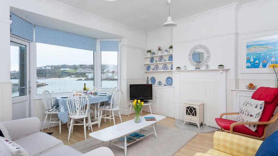 The light and airy sitting room has a nautical theme and contemporary artwork, with a bay window and incorporated door t your private balcony.