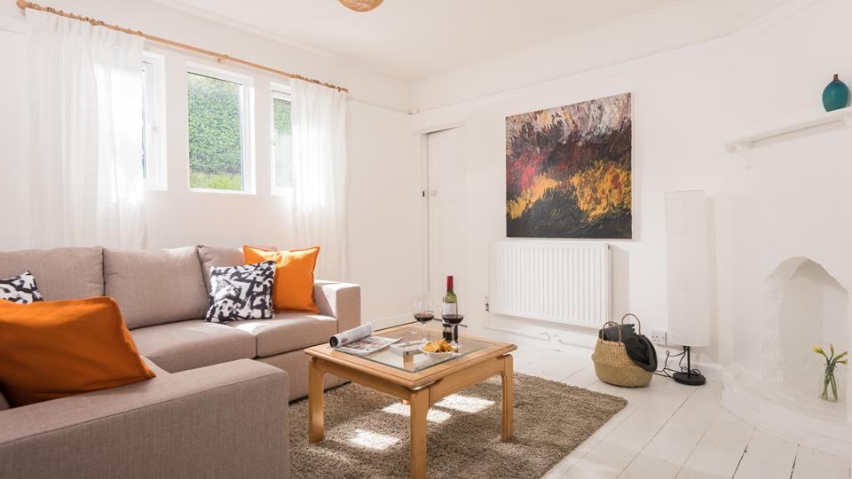 The owner's vibrant artwork, paired with cosy orange cushions adds a warm and welcoming vibe to the minimalistic lounge.