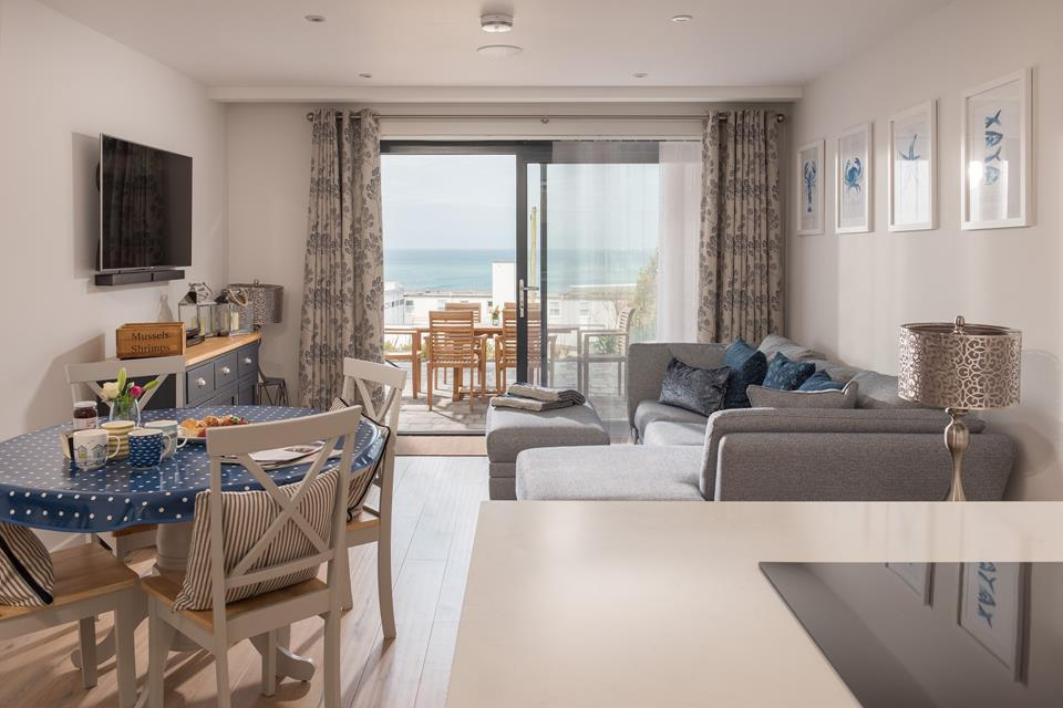 The modern open plan living area with doors out onto the terrace