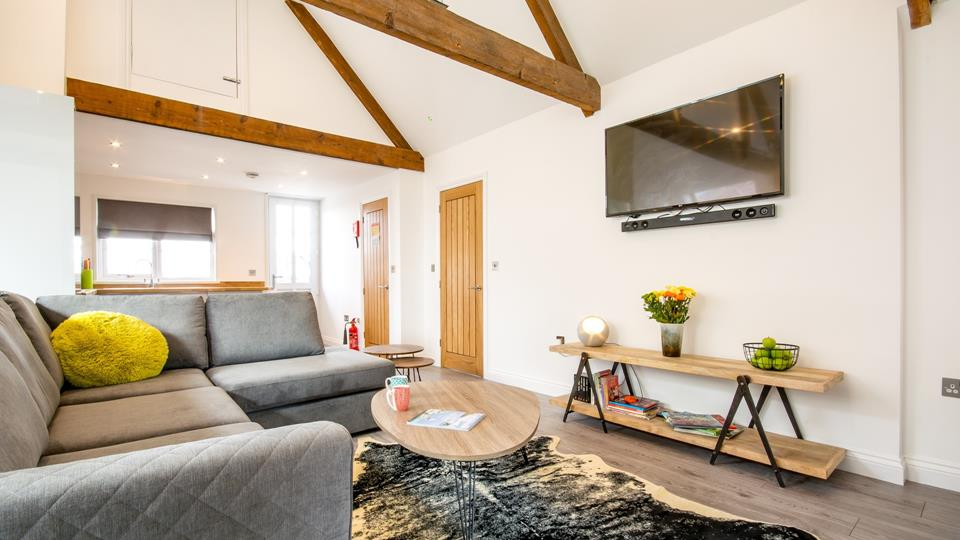 The open-plan living area takes full advantage of the loft apex; the original exposed beams create a light and airy living space.