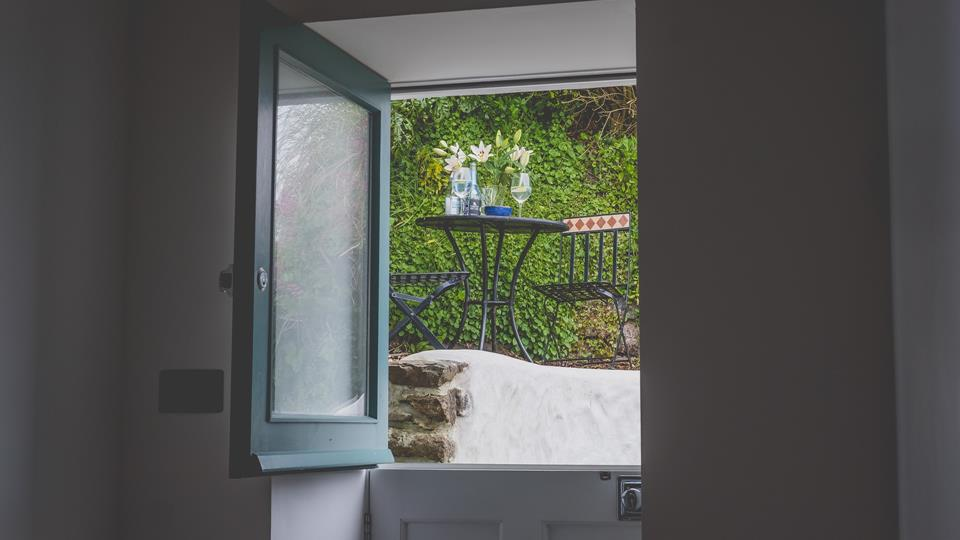 A stable door at the top of the stairs leads out to the back garden where there is a bistro table and sea views.