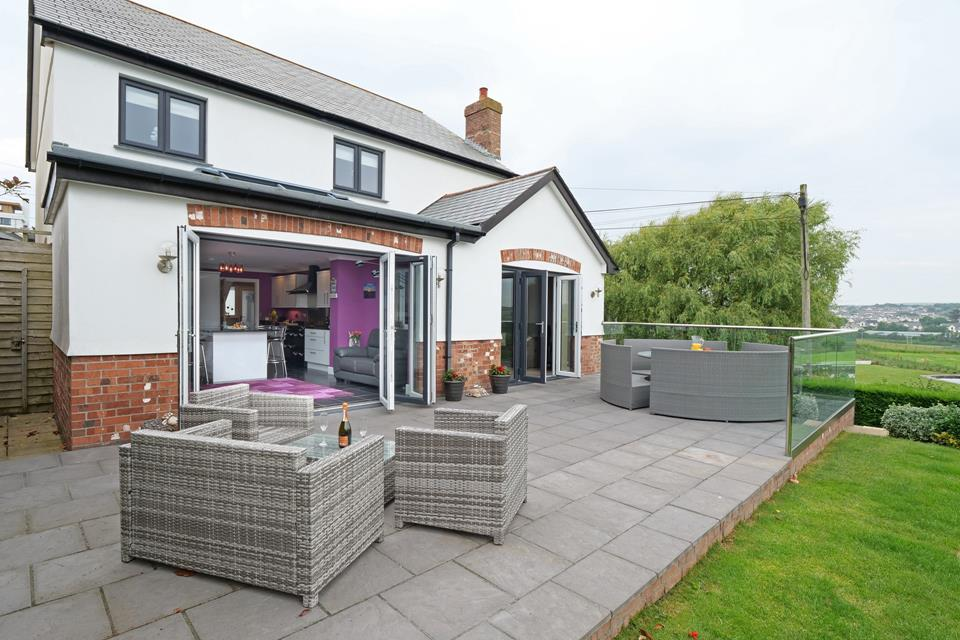 Rear of the property showing patio area with access from bi folds from the sitting room and kitchen/sitting area, fully enclosed garden.