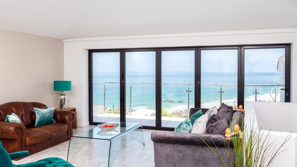 The living space has a stone tiled floor with bi-fold doors onto the glass balustrade balcony with a stunning view over St Ives.