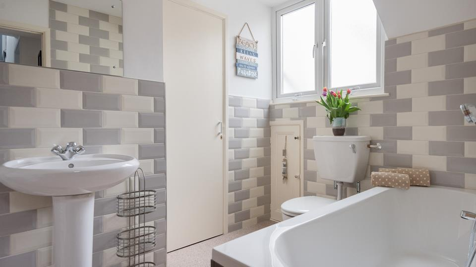 Relax in a bath of bubbles in the spacious bathroom after a day spent exploring the Cornish coast.