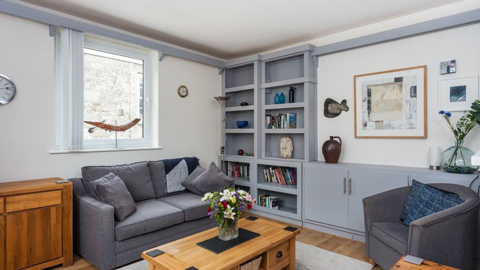 A grey textile sofa and tub chair with natural solid wood coffee table and sideboard unit in the living space.