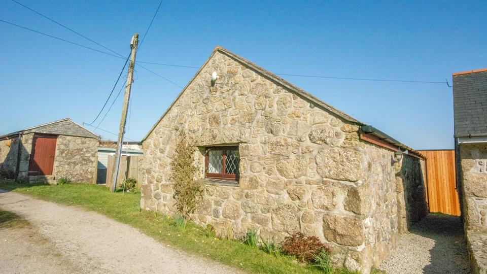 The granite cottage is single-storey and has lead-paned glass windows, a very traditional homestead.