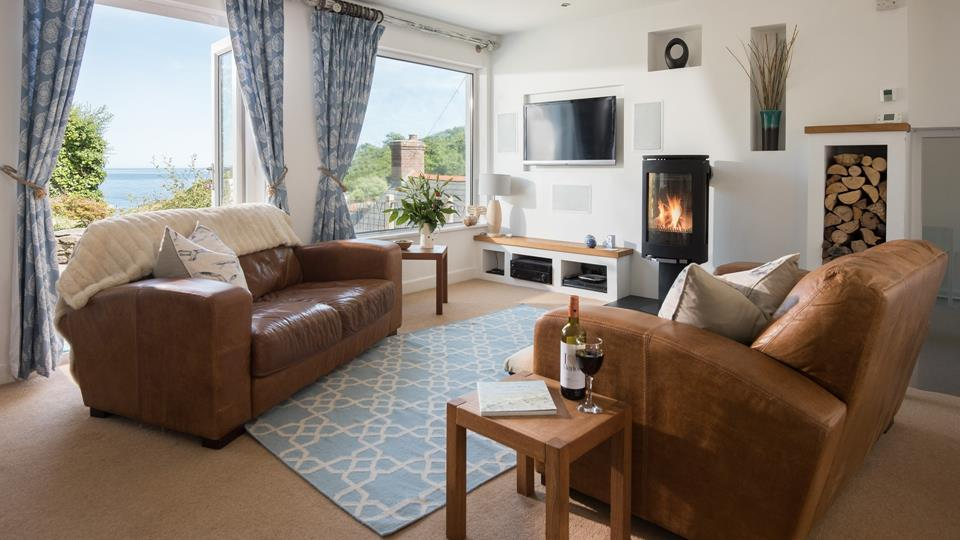 The roaring log burner and sea views compliment each other while you relax on the sofas.