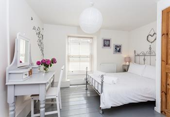 The gracefully designed double bedroom has a restful and romantic decor.