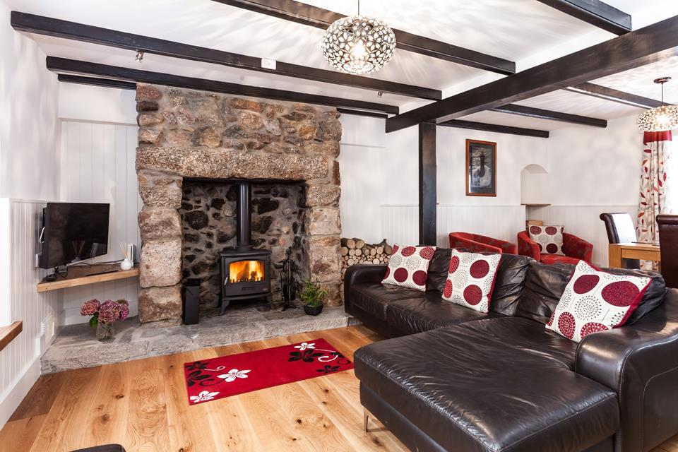 Cosy sitting room with inglenook fireplace and woodburner.