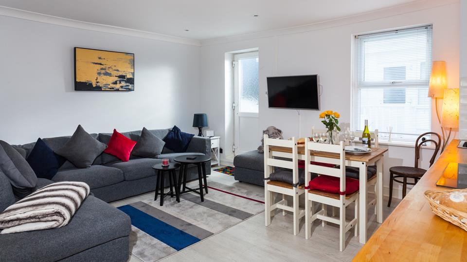 The contemporary open plan living area has lots of modern furnishings and artwork.