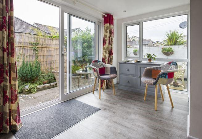 Doors from the open plan kitchen and dining area leading to the enclosed terrace.