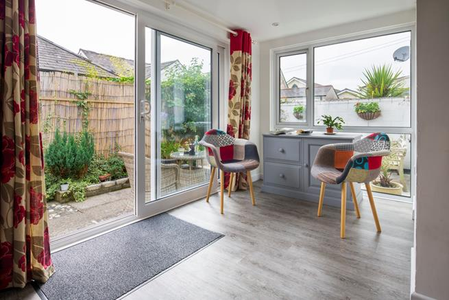 Doors from the open plan kitchen and dining area, lead out to the enclosed terrace at the rear of the house.