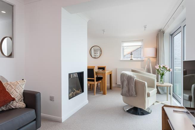 The open plan living area has a lovely electric fire for cosy evenings and doors leading to the balcony for that perfect sunset view.