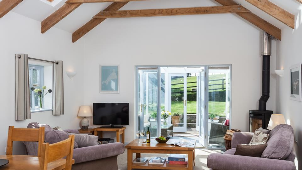 The bright and airy, vaulted ceiling open plan living space is the perfect place to relax, with idyllic views outside.