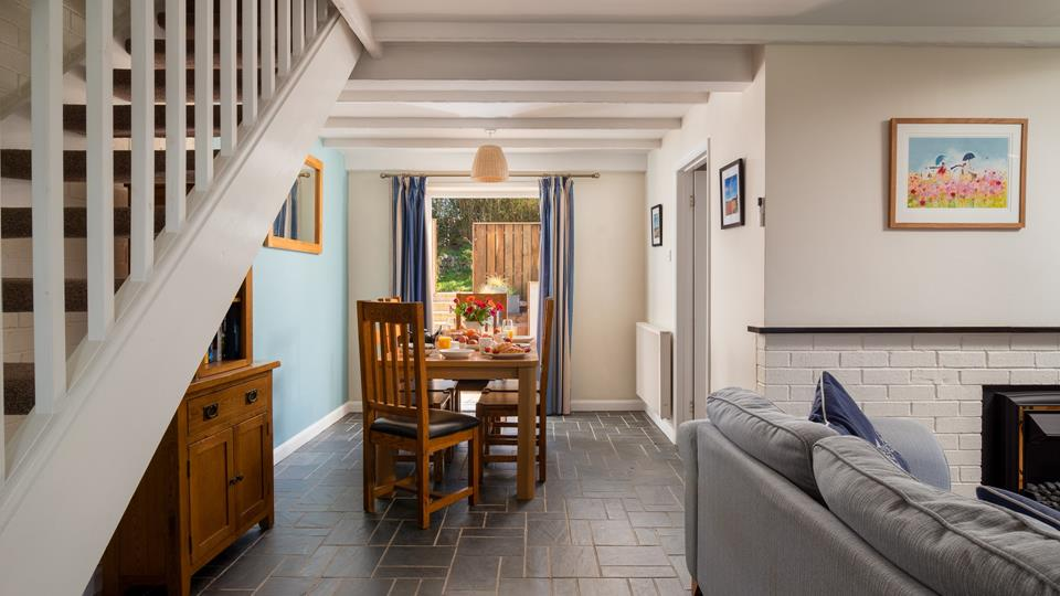 The dining table has 6 chairs, with double doors out to the garden, perfect for enjoying a meal or a board game together.