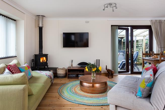 Warm up by the traditional woodburner during colder days or throw open the patio doors during summer days.