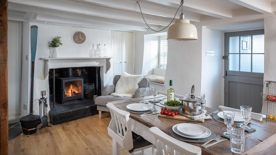 This stunning dining room interior is complete with a woodburner and comfy armchair.