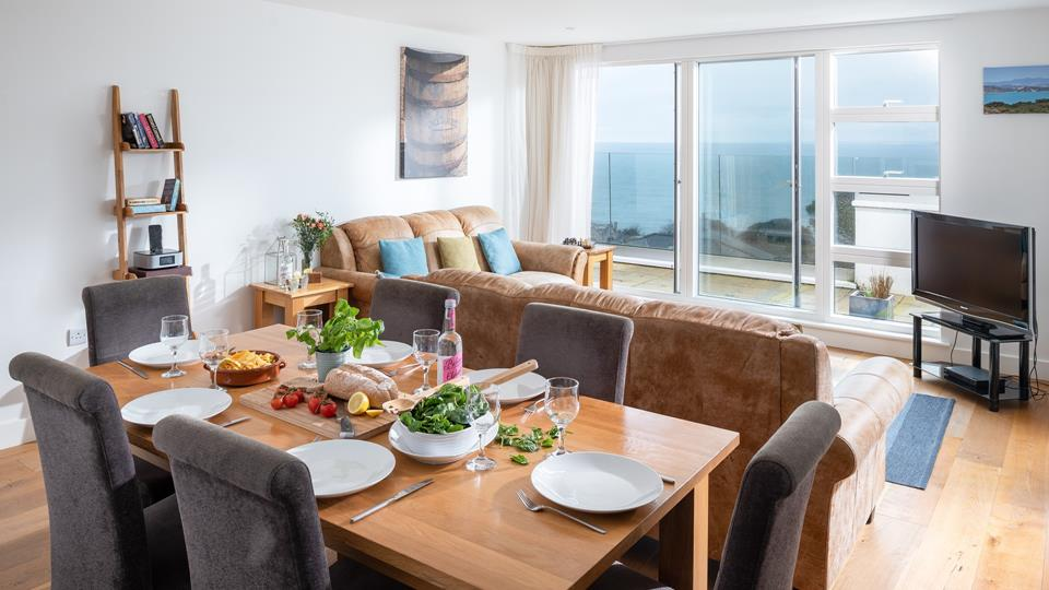 The dining area in the living space has a solid oak wood dining table with textile upholstered dining chairs and natural oak wood flooring throughout.