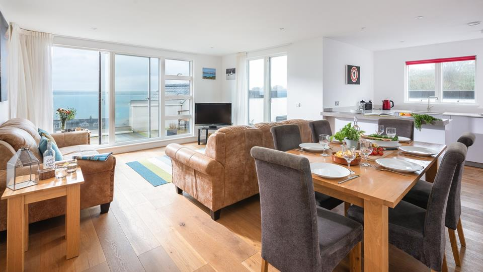 The living space has large sliding patio doors leading out onto the glass frontage balcony with views across Porthminster and the bay.