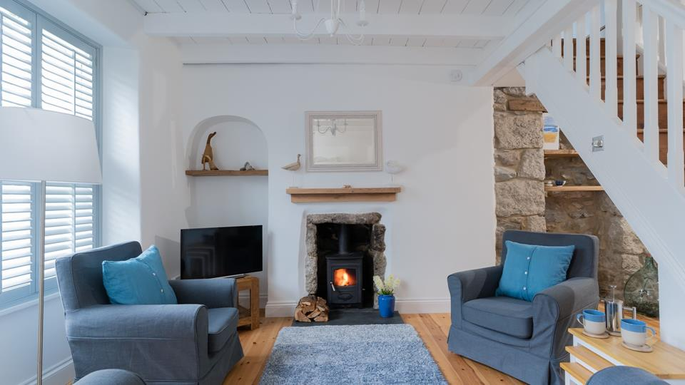 Keep your toes toasty by the woodburner in this large sitting room with stairs up to the bedrooms and bathroom.