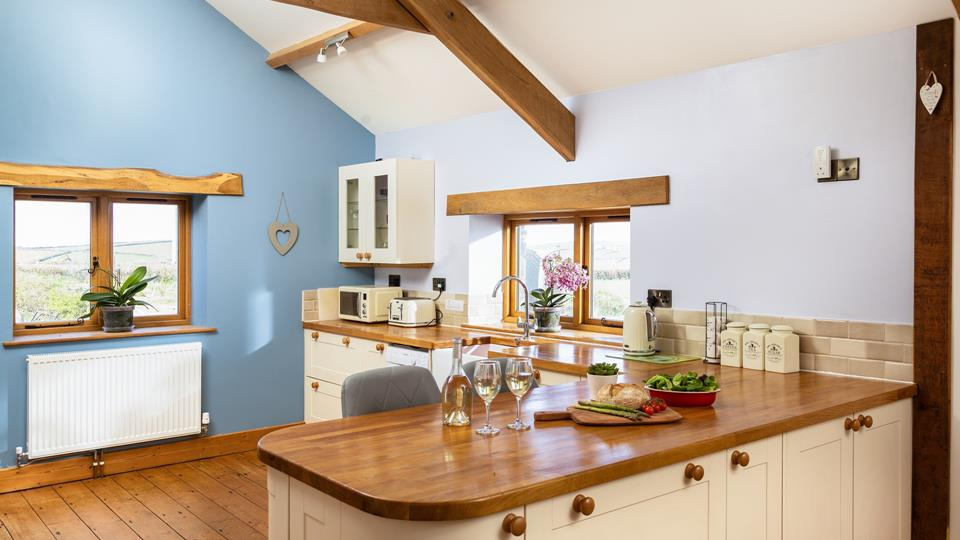 The kitchen has dual aspect windows overlooking the rolling farmland, the wooden work surfaces complement the natural wood lintels and exposed vaulted beam ceilings.