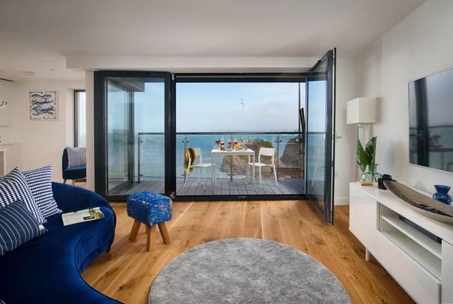 Let the sounds of the sea fill the open plan living space, with the doors opening inwards to make the most of balcony space.