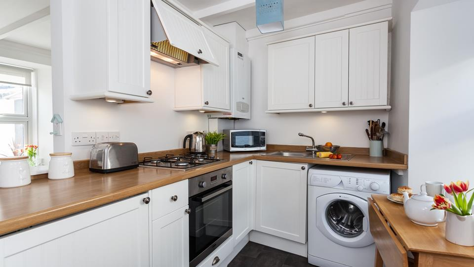The kitchen area has painted wood cupboards with wood effect worktops and has a counter-top microwave.